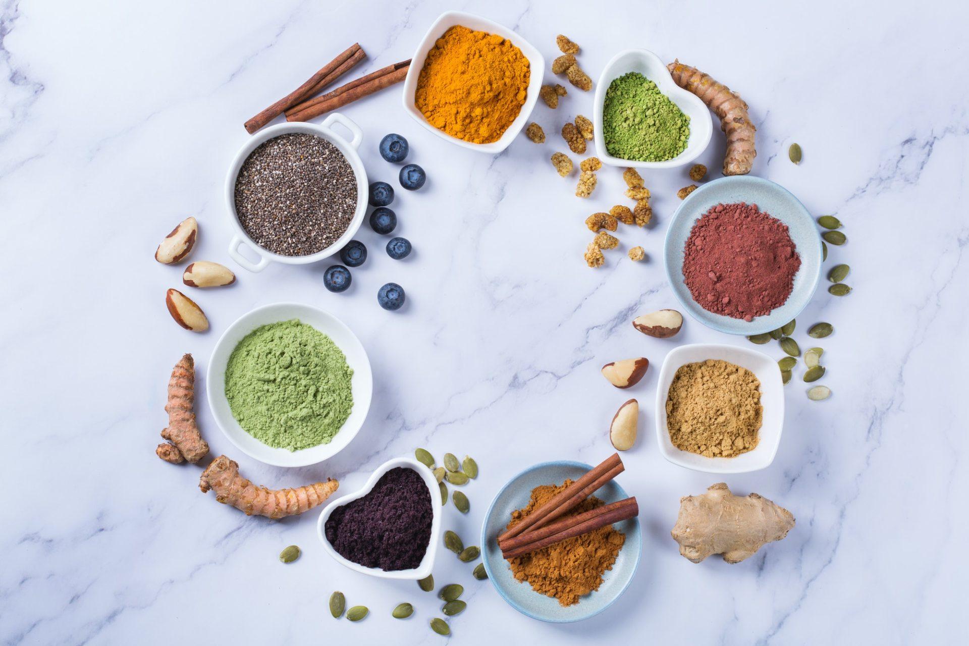 Assortment of superfood powder, acai, turmeric, ginger, matcha, cinnamon, wheat